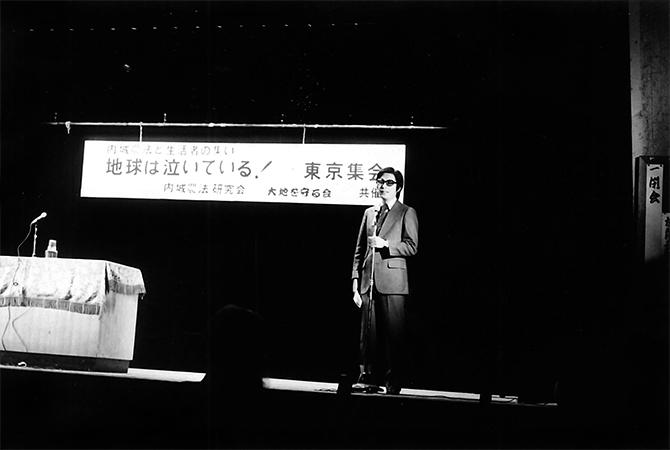 壇上に立つ藤本敏夫さん