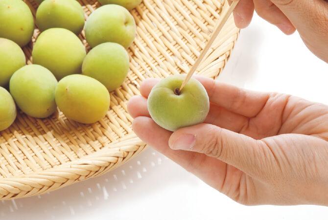 ①梅しごとの最初の一歩。竹串でヘタを取り除く作業。