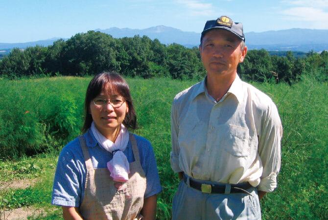 グリーンアスパラガスの生産者、早坂清彦さんとおつれあいの裕子さん。後ろに広がるのはアスパラガスの畑。葉が茂った親茎が、空に向かって元気良く成長中です。
