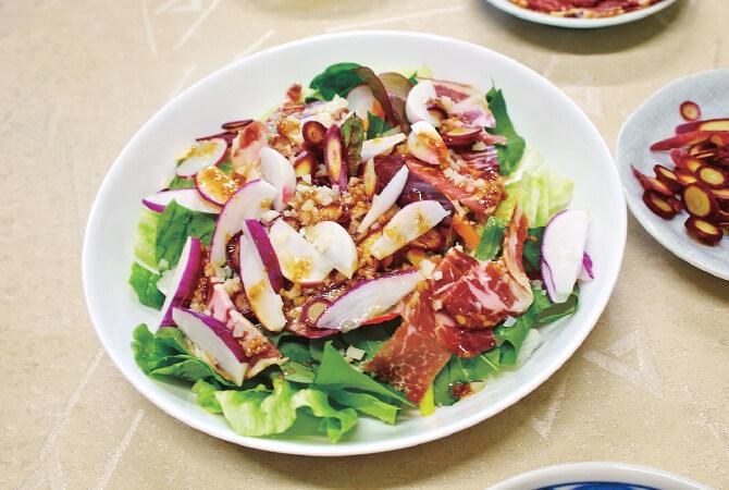賢太郎さんのこの日のサラダ。たっぷりの葉物にチーズや生ハム、ラディッシュをのせて。