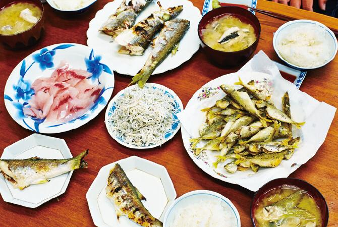 朝5時から漁に出る岩崎家の昼食第一弾。併設する直売所にお客さんがひっきりなしに訪れるため、おつれあいの豊子さんがシラスのパック詰めを行いながら接客。昼食は時間差で食べます。