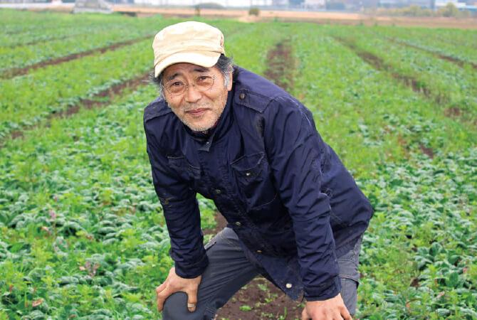山本 稔さん、収穫直前の寒ちぢみほうれんそうと一緒にパチリ。