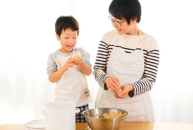 つぶした大豆を混ぜて、丸めて味噌玉にする親子の様子。